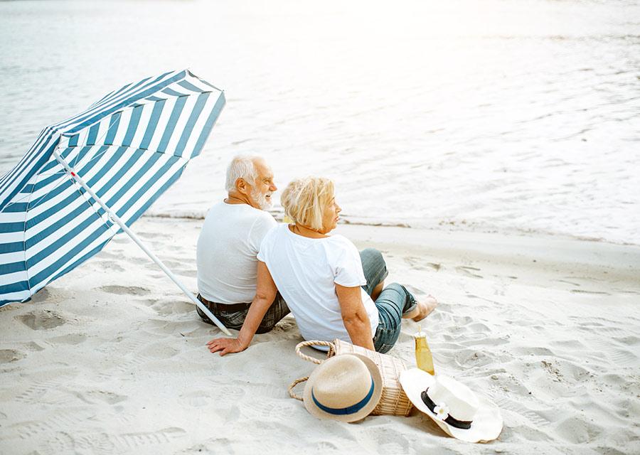 couple sitting by ocean water underneath umbrella successful retirement strategies melbourne fl